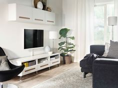 A black and white living room with BESTÅ media storage in white and a black NOCKEBY sofa