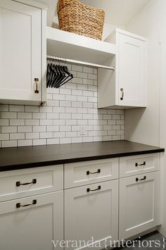 Veranda Interiors: Great laundry area with storage galore. White cabinetry, subway tile backsplash and ...