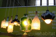 Multi-colored lamps made from repurposed local bottles and glasses with a touch of lace on the outside