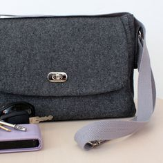 Grey wool satchel style messenger bag suitable for ipad kindle e-reader etc There are three internal pockets The lining is a a blue paisley design