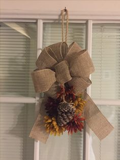Fall burlap decoration  I made this for $3!! Burlap ribbon and flowers from the dollar store and a pine cone from my yard!