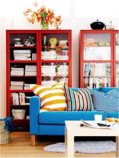 In red Billy bookcases with doors sitting behind a blue couch with striped pillows.