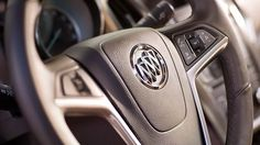 Heated, leather-wrapped steering wheel with premium leather and a chrome trim inside the 2016 Buick Verano small sedan.