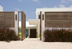dark bronze grasses against rendered white walls and horizontal fence - Cecconi Simone