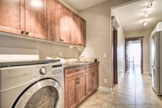Large laundry room with an abundance of cupboard and storage space right off the triple garage. Large Laundry Rooms, Estate Homes, Abundance, Cupboard, Storage Spaces, The Hamptons, Garage, Home Appliances, Clothes Stand
