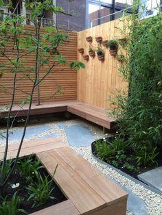 Patio garden with wooden fence, garden bench, flagstones and Yellow Sun split. Garden design by De Peppels tuinontwerp Amsterdam