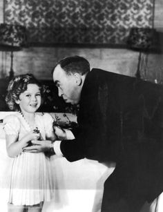"""Shirley Temple Earns a Kid-Sized Oscar - Screenwriter Irvin S. Cobb, host of the 1935 Academy Awards, gives a special, tiny Oscar to Temple for her """"outstanding contribution"""" to the industry in 1934, a year when the 6-year-old star made 12 movies."""