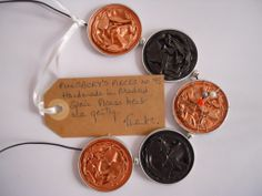 """Pillsbury's Pieces No. 73 - necklace.  Metallic pale apricot coloured and chocolate brown capsules with silver metallic beads on black leather.  Detail is silver coloured wire with natural coloured """"pearl"""", silver grey """"pearl"""" and coral red bead."""