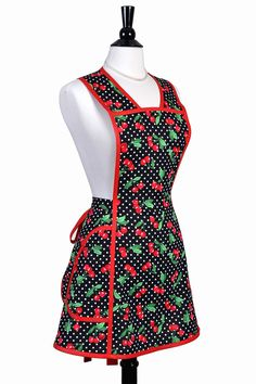 Vintage womens apron features large pockets, cut of the bodice creates a flattering waistline on any size. A perfect gift for her kitchen, apron fabric features red cherries on black and white polka dots. Apron is perfect for cooking or a hostess apron. Apron features over the head