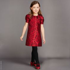 Perfect for smart, formal functions and special occasions, this beautiful jacquard dress by Dolce & Gabbana has a Mini-me print of red flowers on a black background. Lined in silky viscose, it feels luxurious against young skin and little concealed poppers fasten the cuffs of the puffiest puffed sleeves you will have seen all season.