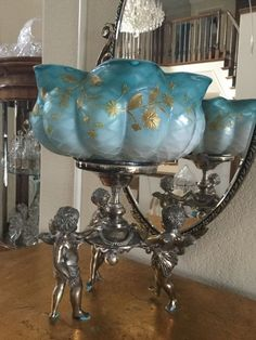 """This beautiful, exceptional bride's basket dates from about 1880. The bowl us held up by three silver plated cupids with their original finish. The Web bowl is satin glass - lovely turquoise color on the outside which gradually fades from the top down and pink on the inside. The bowl is cross- hatched with 24 caret gold flowers weaving around the exterior. It us a special piece with no chips or cracks. This bride's basket stands 13"""" tall. The bowl is 10"""" in diameter and about 4 3/4"""" tall."""