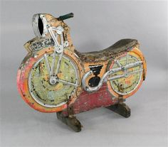 A 1930's English polychrome painted pine speedway fairground ride motorbike, with original handle bars and metal mounts, 39 x 50.5ins  SOLD