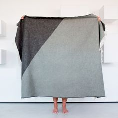 Beautiful grey wool blanket designed by Forestry Wool. The Triangle Dusk Blanket is a luxuriously warm addition to the home made from 100% New Zealand lambswool.