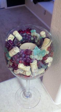 wine inspired candle i made for my new place using a large decorative wine goblet, small bunches of colored grapes, colored glass rocks and wine bottle corks....all items purchased at michaels