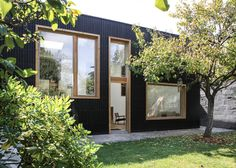 Pale wooden window frames contrast with the black-stained cedar facades of this extension to a detached house in Nantes.