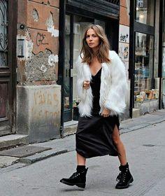 Look com slipdress preto sob faux fur coat e coturno.