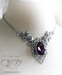 Rich Amethyst purple Swarovski crystal paired with antique silver detailing and grand flourishes make this piece a fantasy to behold. The large pear shaped crystal is about one inch high.     All metal is American-made brass with sterling silver plating.   Features a chain that adjusts from 16
