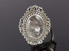 Made with 10x14mm oval rutilated quartz cabochon, sterling silver bezel and wire. Size 8.5
