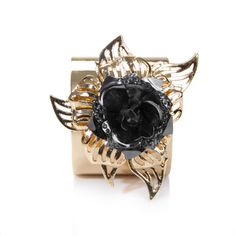 A beautiful shiny gold cuff with a flower made of gold & nickeled silver, dotted with charcoal cz.