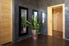 Bonitos los contrastes de madera claro de las puertas, la pared gris y el suelo. Además el toque de la planta le da alegría al recibidor.