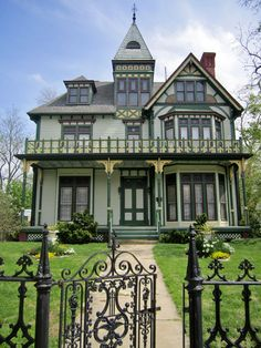 Exquisite Green Mansard-Style Stick Victorian House Design with Pathways  Wrought-Iron Fence