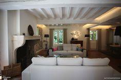 Salon aux poutres apparentes peintes en blanc. Coin cheminée on ne peut plus cosy !