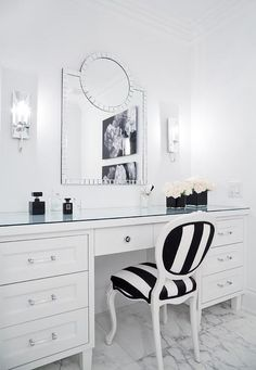 A black and white stripe French chair sits on marble floor tiles at a white makeup vanity accented with nickel and glass pulls and a glass top. White Makeup Vanity, Makeup Vanity Storage, White Vanity, French Vanity, Vanity Drawers, Black Makeup, Vanity Room, Vanity Chairs, Bedroom Vanities