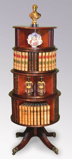 A fine quality 19th Century mahogany 4-tier revolving Bookcase with open shelves fitted with dummy bookspines, supported on reeded 4-splay legs ending on brass castors.  Circa: 1860