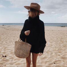 Oversized black sweater. Hat. Straw bag.