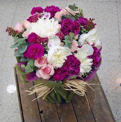 Flores rosas y blancas en jarrón.