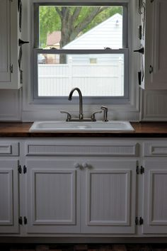 Grand Kitchen Reveal....Finally!!!!! We used bead board wallpaper and small trim on the flat faced cabinet doors.