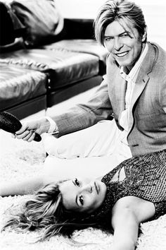 [Image is a photo of David Bowie sitting on the floor next to Kate Moss, who's laying down. Bowie's holding a hairbrush and smiling, while Kate Moss looks neutral. End description. Ellen Von Unwerth, Kate Moss, Kiko Mizuhara, Tim Walker, Claudia Schiffer, Cindy Crawford, David Jones, David Bowie T Shirt, The Thin White Duke