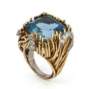 Light blue stone set in gold ring with diamond casings