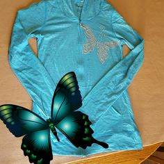 NWOT lightweight blue sweatshirt w/ butterfly NWOT but I cut the tag on the inside off (see second photo) lightweight blue sweatshirt with rhinestone butterfly accent (none missing). size large but FITS LIKE A SMALL, maybe medium Tops Sweatshirts & Hoodies