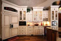 Custom Kitchen Cabinets by Walker Woodworking. The paneled refrigerator and glass doors add a nice touch to this French Country style.