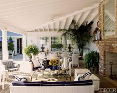 The poolhouse features sofas from Janus et Cie with Sunbrella-fabric cushions, leather ottomans by Nancy Corzine, and a cocktail table and embroidered pillows by Lorin Marsh.