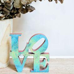 """Ya lo decía John Lennon: """"All you need is love"""". ¡Gran verdad! Y si además el amor viene con una pizca de pop art y otro poco de glamour… ¡nos apuntamos! Con la palabra de madera 'Love' de 27 lletres, vestirás tu casa de arte y de sentimiento. Empieza a buscar un hueco para esta escultura, porque estamos seguros de que te va a enamorar.   La palabra de madera 'Love' de 27 lletres es una escultura hecha a mano en madera recuperada y pintada con pinturas al agua. Está disponible en 3 colores…"""