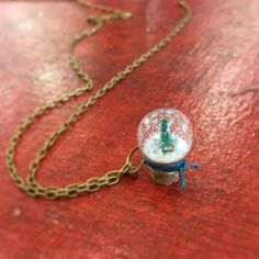 A tiny snow globe necklace. Kits and how-to are available at Ornamentea in Raleigh. This will the be free First Friday project on Friday, December 3rd, 2015. #raleigh #firstfriday #snowglobe #diy #glitter