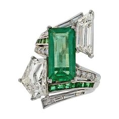 This dynamic, large-scale, adaptation of the classic platinum bypass ring is designed around a vivacious, bright green, elongated emerald-cut emerald weighing carats. The emerald is asymmetrically framed by two large fancy-cut diamonds: an epaulet-cu Art Deco Schmuck, Bijoux Art Deco, Art Deco Jewelry, Vintage Jewelry, Jewelry Design, Antique Jewelry, Emerald Jewelry, Gems Jewelry, Diamond Jewelry