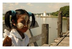 Myanmar.  Tanaka powder is obtained from tree bark and mixed with water and oils to form a paste that is applied liberally to the face and arms to protect against the sun.   I can only think that this little girl was going to a festive occasion.