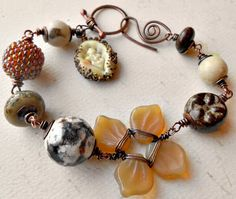 Autumn bracelet featuring lampwork leaf by Karen Leonardo, beaded bead by Kristen Stevens, ceramic bead by Karen Totten, lampwork raku bead by Sue Kennedy, agate, bronzeite, and wired Czech-glass flower with copper.