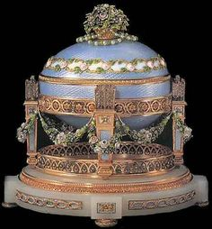 """1907 / Love Trophies Egg, also known as """"Cradle with Garlands Egg"""", is made of varicolored gold, translucent pale blue & green enamel, opalescent oyster enamel, diamonds, rubies, pearls, white onyx & a silk-lining. The missing surprise was possibly children portraits.  It is supported in a gold cradle by four columns (Cupid's arrows set with diamonds); that on a carved oval white onyx base & four bun feet in gold."""