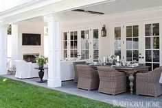 This long patio is divided into a dining space and a sitting area by a fireplace. Delightful! - Traditional Home ® / Photo: Michael Garland / Design: Lonni Paul