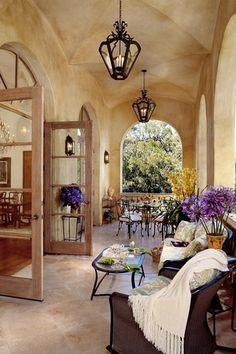 Mediterranean Porch with Transom window, exterior stone floors, Wrap around porch, Deck Railing, French doors
