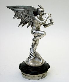 1923 Mephisto, Devil Car Mascot Hood Ornament ; Mephisto (Devil cocking snoot). Art Deco mascot signed by Podiebrad. Silvered bronze, fantastic detail, rare mascot made in c.1923. The original advertising catalogue page from the Auto Omnia 1923 catalogue is reproduced on page 19, Michel Legrand book 'Mascottes Automobiles' also photographed and described on Plate 416.
