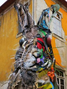 Bordalo II (previously) has created a series of bisected animals, colorful plastics forming one half of the creature while a combination of wood and metal created a muted mirror on the other side. In one piece the Portuguese artist created a turtle with legs that extend to the ground, appearing to c