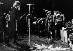 """""""Mick Jagger looks on as the Hells Angels drag their victim's body onstage during the concert. After Hunter's attack, The Stones left the stage, fleeing in helicopters that awaited them. They landed minutes afterwards, shell-shocked, in an LA airport terminal."""""""