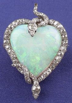 Edwardian Platinum, Opal, and Diamond Snake Pendant/Brooch, designed as a heart-shaped opal entwined by two old mine and old European-cut diamond serpents, (with removable 14kt gold pinstem).