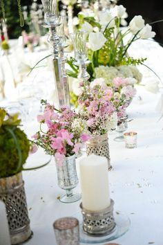 L'argenteria, magari scovata nei mercatini, contiene fiori e candele.