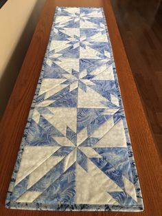 This beautiful Blue and Silver table runner will brighten up your table for Christmas and all through the winter season. The shades of blue fabric and silver metallic make this table runner sparkle. The white fabric has a snowflake pattern on it. These quality cotton fabrics are absolutely gorgeous together. The backing is a very pretty snowflake print in blues and greens which makes this table runner reversible. Details:  - 48 x 12.25 inches - Made with quality 100% cotton fabric - Machine…